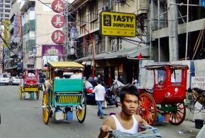 Horsedrawn calesas plying Ongpin Street, at the heart of Manila's Chinatown
